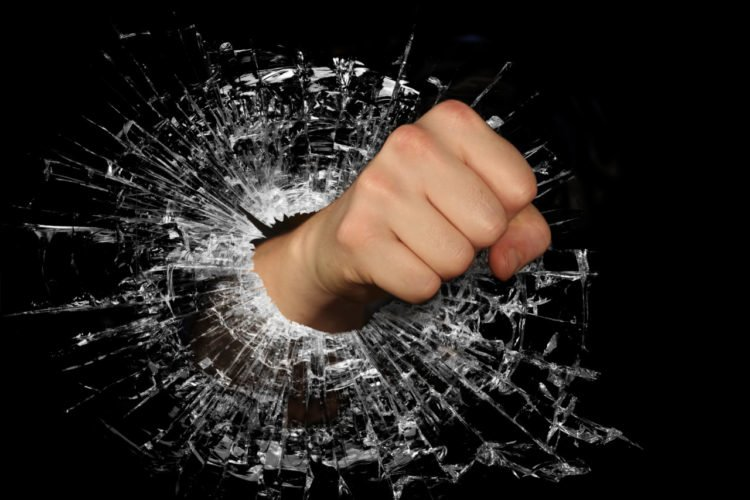 A fist punching through glass. Learn how to deal with road rage to make sure this doesn't happen.