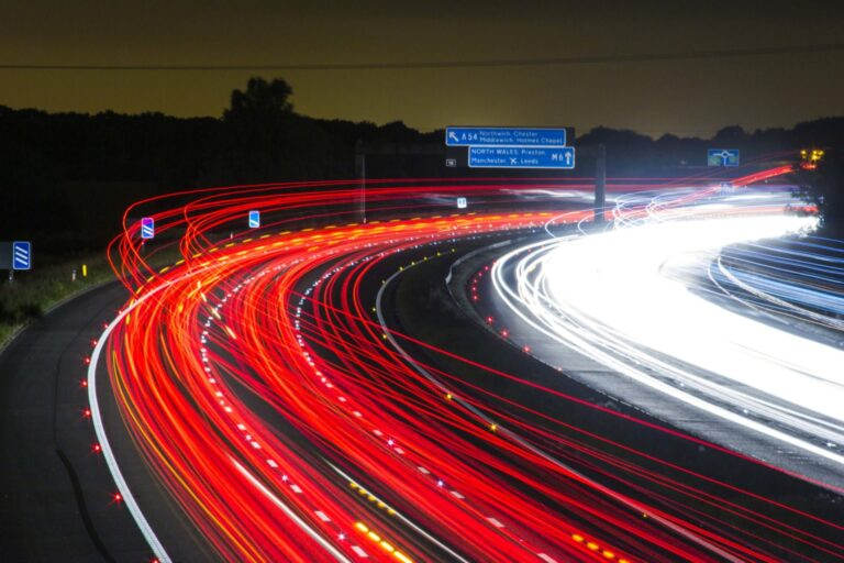 A long exposure of cars driving at night, creating long trails of light in the night sky.