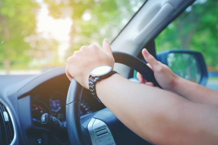 Picture showing someone driving with hands on the steering wheel