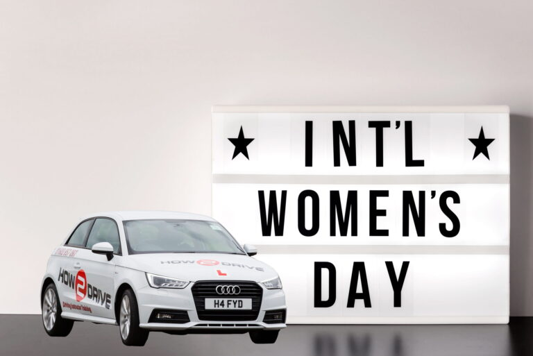 Picture showing International Women's Day sign and a How-2-Drive car