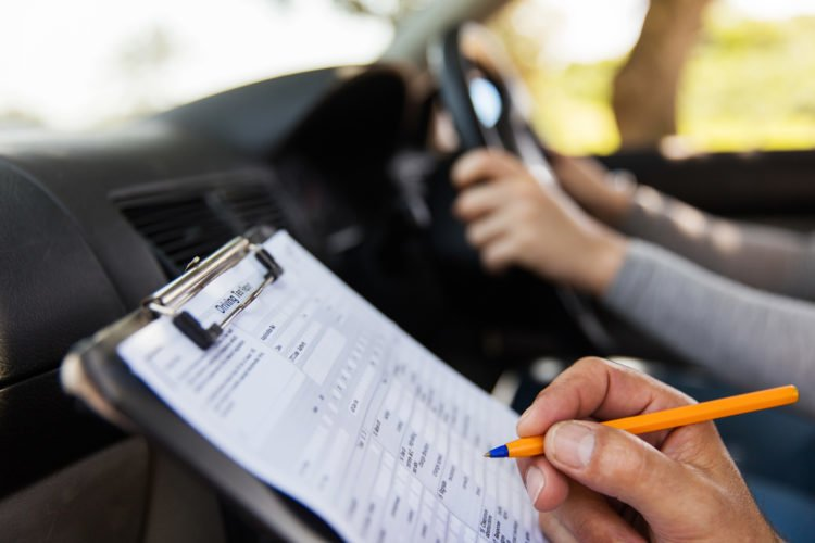 Picture shows an examiner marking a learner in their driving test