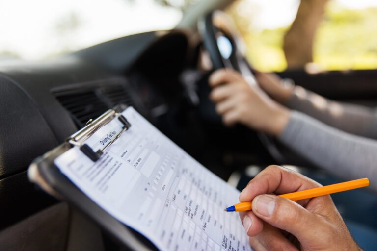 An examiner marking a learner who is taking their driving test.