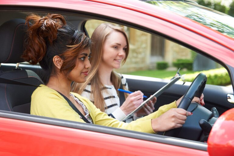 A female driving instructor teaching a learner driver.