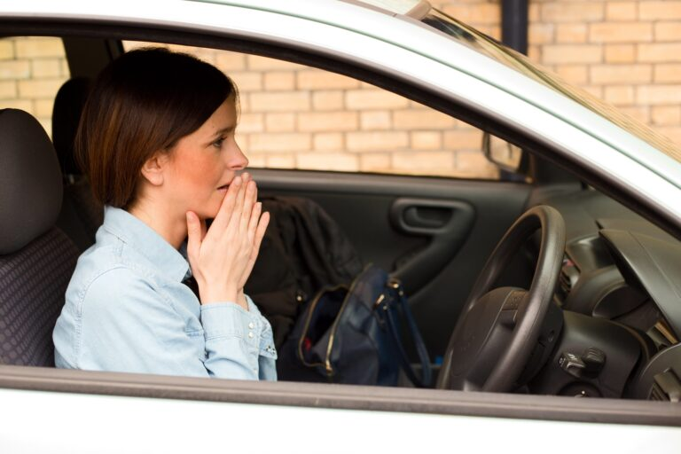 Picture showing a woman looking worried at the wheel