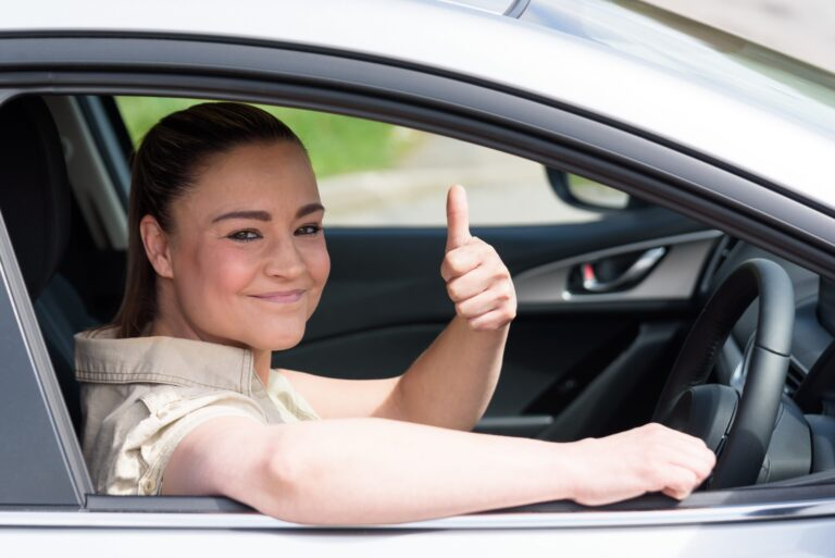 A woman with her thumbs up after beating her driving test nerves and passing successfully!