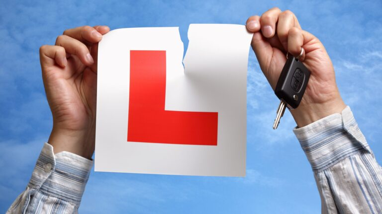 A man tearing up his L-plate, symbolising that exciting moment when you pass your test.