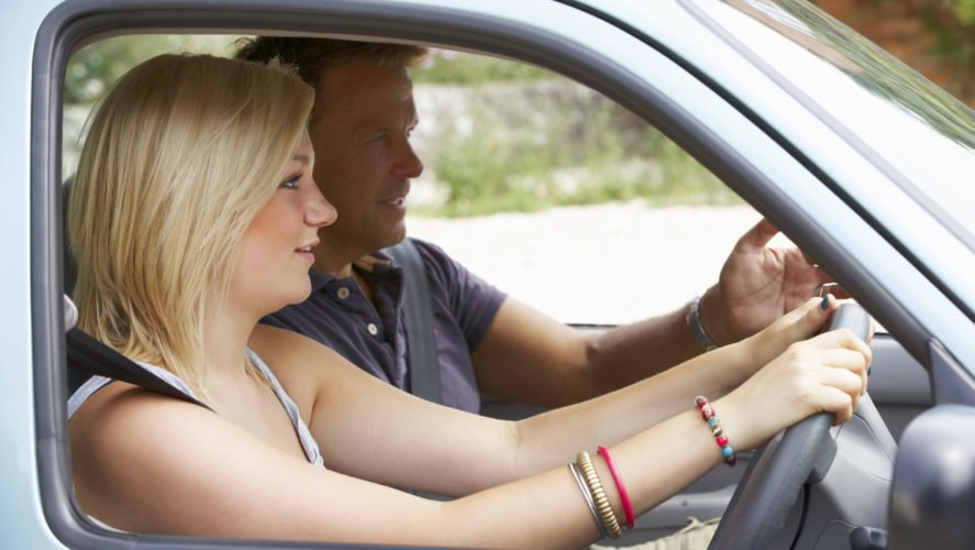 A woman taking a refresher driving lesson with her driving instructor.