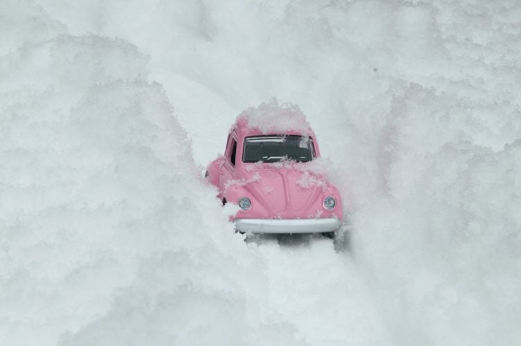 A toy VW Beetle trying to drive through deep snow.