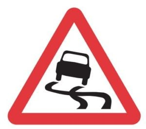 Triangular warning sign depicting a slippery road surface.