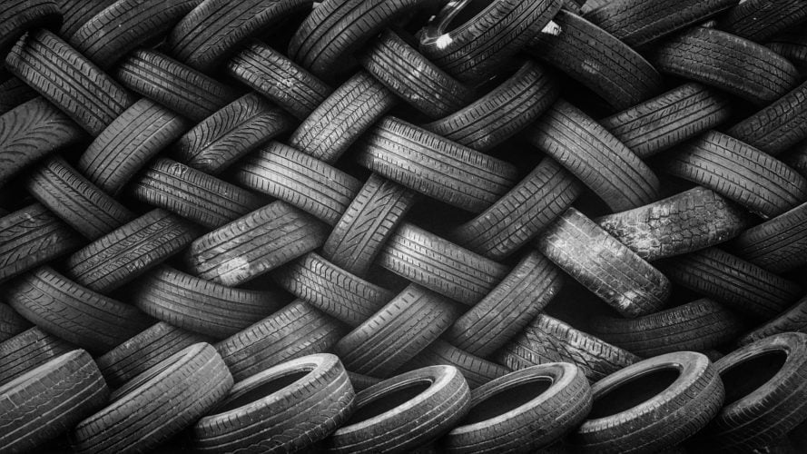 A wall of used car tyres. Tyres are one of the most common car maintenance replacement parts.