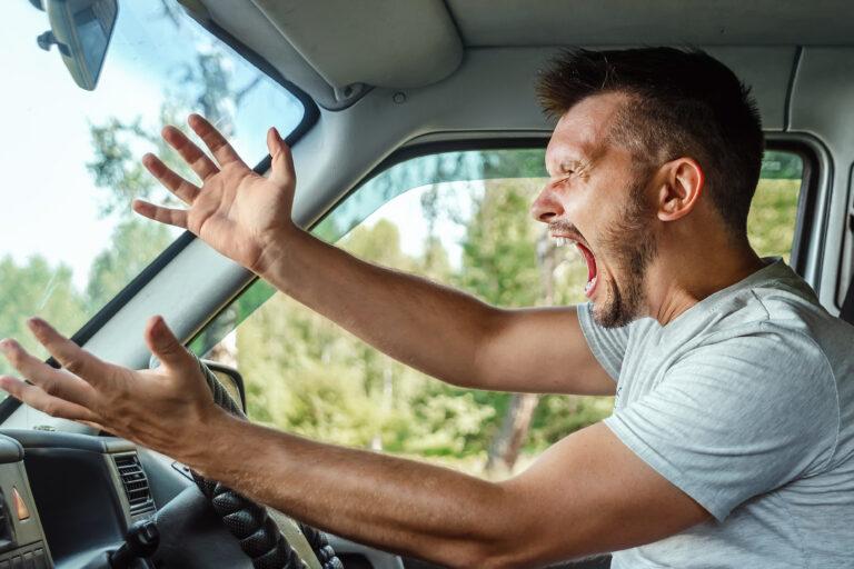 An angry man driving his car, symbolising road rage.