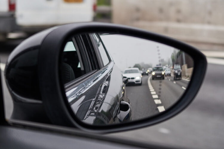 A car door mirror showing lanes of traffic behind. Learning to use your mirrors safely is part of the MSPSL routine.